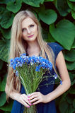Blonde kaukasische Frau, die einen Kornblumeblumenstrauß hält Stockbild