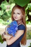 Blonde kaukasische Frau, die einen Kornblumeblumenstrauß hält Lizenzfreie Stockfotografie