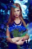 Blonde kaukasische Frau, die einen Kornblumeblumenstrauß hält Stockfotos