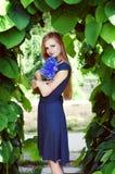 Blonde kaukasische Frau, die einen Kornblumeblumenstrauß hält Stockbilder