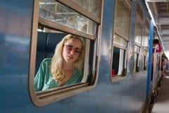 Blonde kaukasische Frau, die einen Zug, Abflussrinnenfenster schauend reitet Stockbild