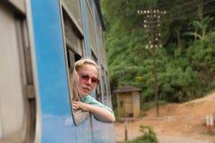 Blonde kaukasische Frau, die einen Zug, Abflussrinnenfenster schauend reitet Stockfotografie