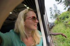 Blonde kaukasische Frau, die einen Zug, Abflussrinnenfenster schauend reitet Lizenzfreie Stockfotografie