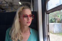 Blonde kaukasische Frau, die einen Zug, Abflussrinnenfenster schauend reitet Stockfoto