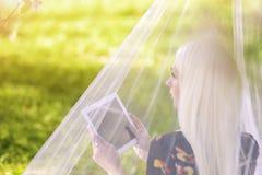 Blonde kaukasische Frau, die im Frühjahr persönliches Tablet Forest Ou verwendet Lizenzfreies Stockfoto