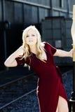 Blonde kaukasische Frau im Freien im roten Kleid Stockbilder