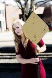 Blonde kaukasische Frau im roten Kleid, das an hält, um Zeichen gelb zu färben Stockfotografie