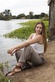 Blonde kaukasische Frauen-Sitzen im Freien entlang Fluss Stockfoto