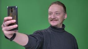 Blonde Kaukasische gepensioneerde in grijze trui die selfie-foto's op smartphone nemen en op groene achtergrond glimlachen stock video