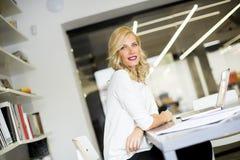 Blonde kaukasische Geschäftsfrau, die in ihrem Büro arbeitet Stockfotos
