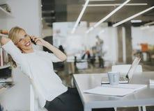Blonde kaukasische Geschäftsfrau, die an ihrem Büro und an speakin arbeitet Lizenzfreies Stockbild