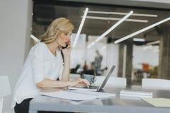 Blonde kaukasische Geschäftsfrau, die an ihrem Büro und an speakin arbeitet Stockbilder