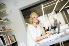 Blonde kaukasische Geschäftsfrau, die ihren Handy und sitti verwendet Stockbild