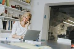 Blonde kaukasische Geschäftsfrau, die ihren Handy und sitti verwendet Stockbilder
