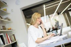 Blonde kaukasische Geschäftsfrau, die ihren Handy und sitti verwendet Stockfotografie