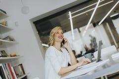 Blonde kaukasische Geschäftsfrau, die ihren Handy und sitti verwendet Lizenzfreies Stockfoto