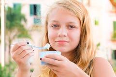 Blonde kaukasische Jugendliche isst gefrorenen Jogurt Stockfotografie