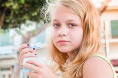 Blonde kaukasische Jugendliche mit gefrorenem Jogurt Stockfoto