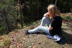 Blonde kaukasische Jugendliche sitzt im Wald Lizenzfreie Stockfotos