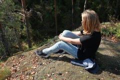Blonde kaukasische Jugendliche sitzt im Wald Stockfotografie