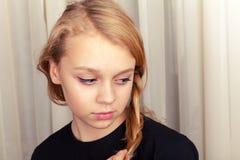 Blonde Kaukasische meisjesglimlachen schuchter, close-upportret Royalty-vrije Stock Foto's