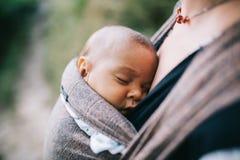 Blonde kaukasische Mutter, die ihr farbiges Kind in einem Riemen hält Lizenzfreie Stockfotos