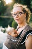 Blonde kaukasische Mutter, die ihr farbiges Kind in einem Riemen hält Stockbild