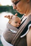 Blonde kaukasische Mutter, die ihr farbiges Kind in a hält und berührt Stockfoto
