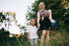 Blonde kaukasische Mutter mit ihren zwei farbigen Kindern warten Hand in Hand Stockbild