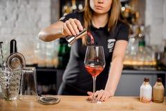 Blonde Kellnerin, die Cocktail am Barzähler unter Verwendung der Barutensilien tut Stockfotos