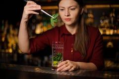 Blonde Kellnerin in einem roten Kleid bereitet ein mojito vor, das Blätter von hinzufügt Stockfoto