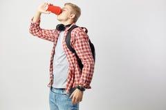 Blonde kerel in hoofdtelefoons, met zwarte rugzak op zijn schouders gekleed in een witte t-shirt, een rode geruite overhemd en je stock foto