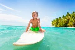 Blonde Kinderschwimmen auf Brandungsbrett im klaren Meer Stockbild
