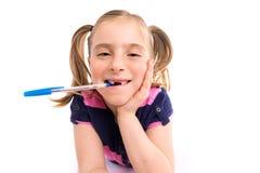Blonde Kinderstudentin mit gewundenem Notizbuch im Schreibtisch Lizenzfreie Stockfotografie