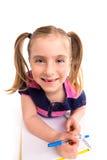 Blonde Kinderstudentin mit gewundenem Notizbuch im Schreibtisch Lizenzfreie Stockfotos