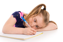 Blonde Kinderstudentin mit gewundenem Notizbuch im Schreibtisch Stockbild