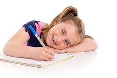 Blonde Kinderstudentin mit gewundenem Notizbuch im Schreibtisch Stockbilder