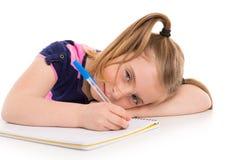Blonde Kinderstudentin mit gewundenem Notizbuch im Schreibtisch Stockfotos