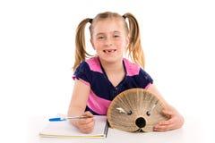 Blonde Kinderstudentin mit Igelbuch Stockfotos