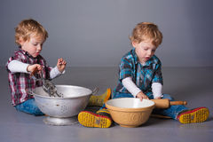 Blonde Kleinkinder, die mit Kochgeräten spielen Stockfoto