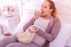 Blonde knappe zwangere vrouw in comfortabele kleren die een snack hebben royalty-vrije stock afbeelding