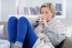 Blonde kranke Frau, die auf Couch mit Becher legt Lizenzfreie Stockbilder