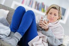 Blonde kranke Frau, die auf Couch mit Becher legt Lizenzfreies Stockbild