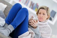 Blonde kranke Frau, die auf Couch mit Becher legt Stockbilder