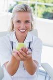Blonde Krankenschwester, die einen grünen Apfel hält Lizenzfreies Stockfoto