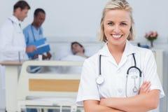 Blonde Krankenschwester, die ihre Arme kreuzt Stockbild