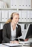 Blonde Kundendienst-Exekutive, die Kopfhörer verwendet Stockfotos