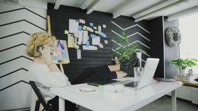 Blonde kurzhaarige Geschäftsfrau, die am Telefon spricht und mit den Beinen auf Tabelle sitzt stock video footage