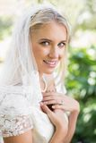 Blonde lächelnde Braut in einem Schleier, der ihre Hände zu ihrem Kasten hält Stockfotografie