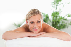 Blonde lächelnde Frau, die auf einem Nichtstuer sich entspannt Stockbilder